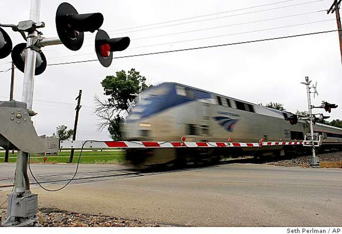 FILE - In this Sept. 13, 2006, file photo an Amtrak passenger train passes through a crossing near Sherman, Ill., along an upgraded stretch of track designed to move trains faster between the Illinois' capital and Chicago. High-speed rail plans in the Midwest and California appear to be the front runners in the race for $8 billion in stimulus cash, with selection criteria released by the Obama administration on Wednesday, June 17, 2009, seeming to favor them. (AP Photo/Seth Perlman, File)