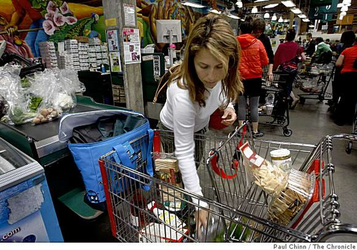 Karla Camer places her groceries on the checkout counter at Rainbow Grocery in San Francisco, Calif., on Thursday, June 11, 2009. Camer saved 20 percent on her purchases by using a discount coupon that she clipped from the phone book.
