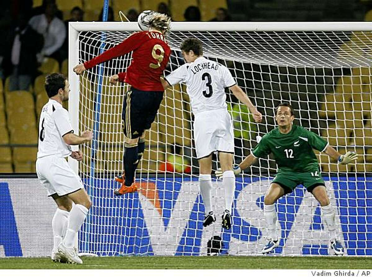 Spain's Fernando Torres, second from left, scores his third goal as New Zealand's goalkeeper Glen Moss, right, looks at him while Tony Lockhead, second from right, and Tim Brown, left, try to defend, during their Confederations Cup Group A soccer match at the Royal Bafokeng Stadium in Rustenburg, South Africa, Sunday, June 14, 2009. (AP Photo/Vadim Ghirda)