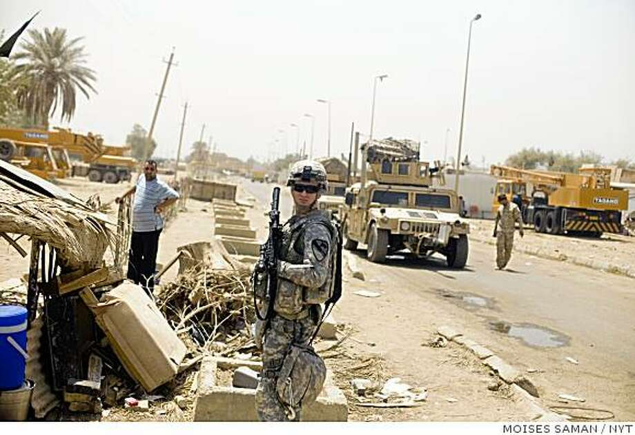 A U.S. soldier from Bravo Company, 1-5 Cavalry stands near the scene of a bombing in the Bab al-Sheikh district of Baghdad thak killed at least 19 people, Friday morning June 26, 2009.  A  booby-trapped motorcycle loaded with nails and ball-bearings exploded in a crowded bazaar Friday in Baghdad, killing at least 19 people and wounding 50, Iraqi officials said. The attack occurred just four days before the deadline for U.S. combat troops to withdraw from cities. (Moises Saman/The New York Times) Photo: MOISES SAMAN, NYT