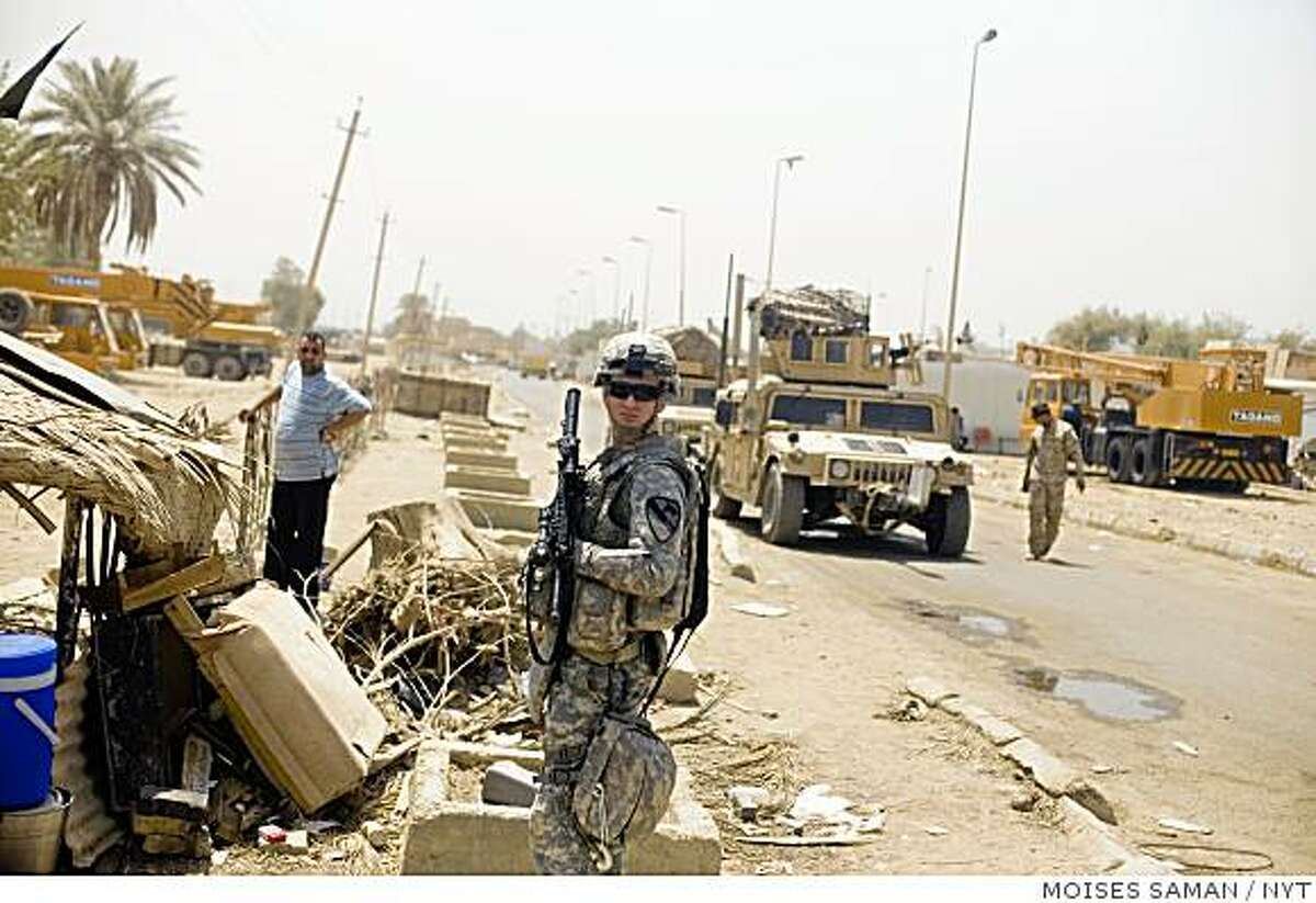A U.S. soldier from Bravo Company, 1-5 Cavalry stands near the scene of a bombing in the Bab al-Sheikh district of Baghdad thak killed at least 19 people, Friday morning June 26, 2009. A booby-trapped motorcycle loaded with nails and ball-bearings exploded in a crowded bazaar Friday in Baghdad, killing at least 19 people and wounding 50, Iraqi officials said. The attack occurred just four days before the deadline for U.S. combat troops to withdraw from cities. (Moises Saman/The New York Times)