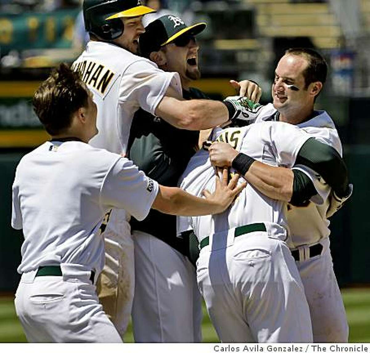 Teammates mob Rajai Davis after Davis hit a game-winning single to score Chris Denorfia in the bottom of the ninth inning of play. The Oakland Athletics played the Minnesota Twins at the Oakland-Alameda County Coliseum in Oakland, Calif., on Thursday, June 11, 2009, in their final game of the series. The Athletics won the game 4-3.