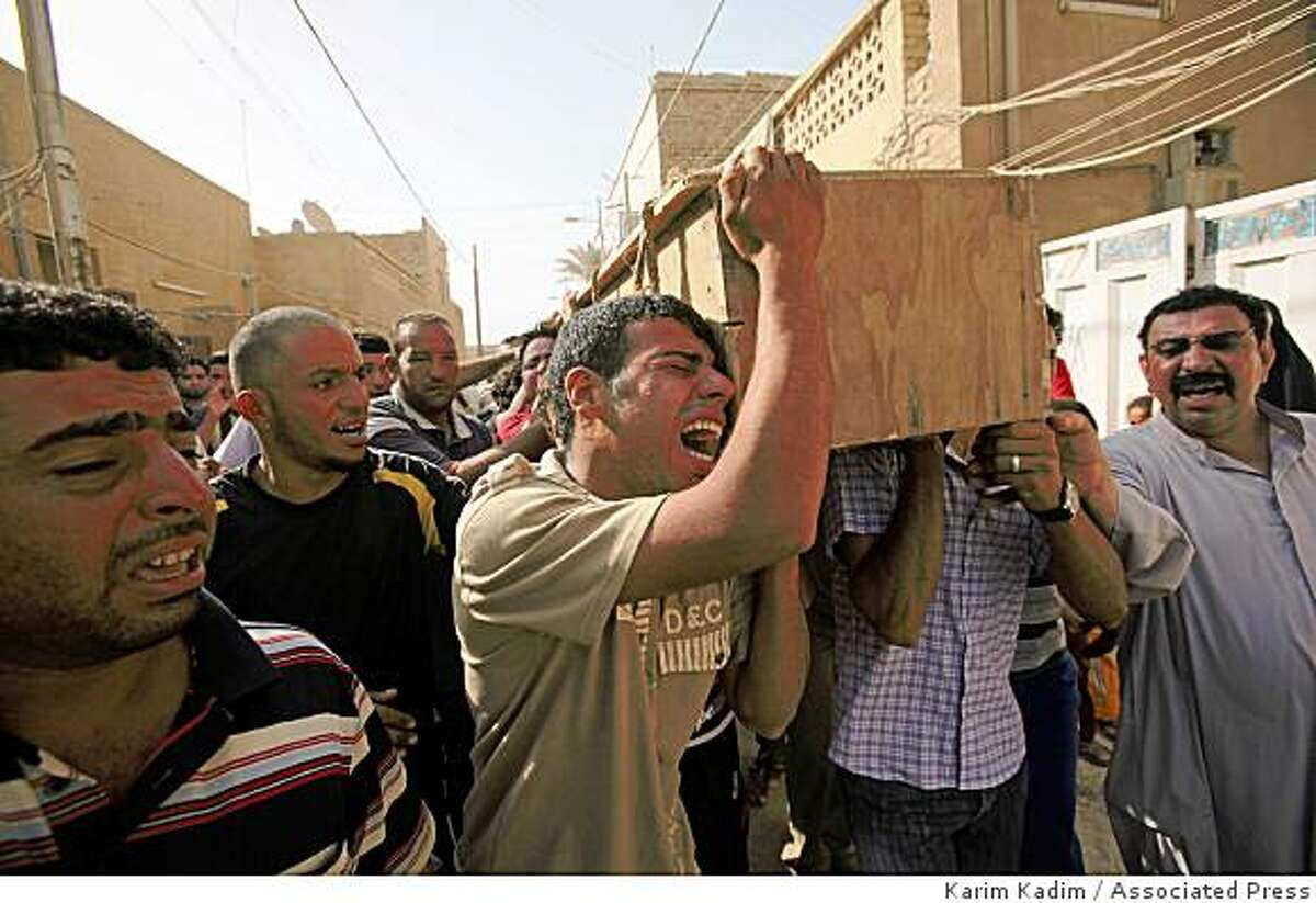 Men carry the coffin of a relative killed in a bombing in the main Shiite district in Baghdad, Iraq, Thursday, June 25, 2009. A bomb ripped through a crowded market on Wednesday, less than a week before a deadline for U.S. combat troops to leave Iraq's urban areas.