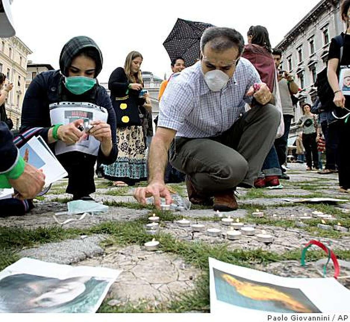 Activists light candles during a demonstration against the violence in Iran, at the G8 foreign ministers' meeting in Trieste, Italy, Thursday, June 25, 2009. Italy hopes foreign ministers of the industrialized Group of Eight meeting Thursday will send Iran a