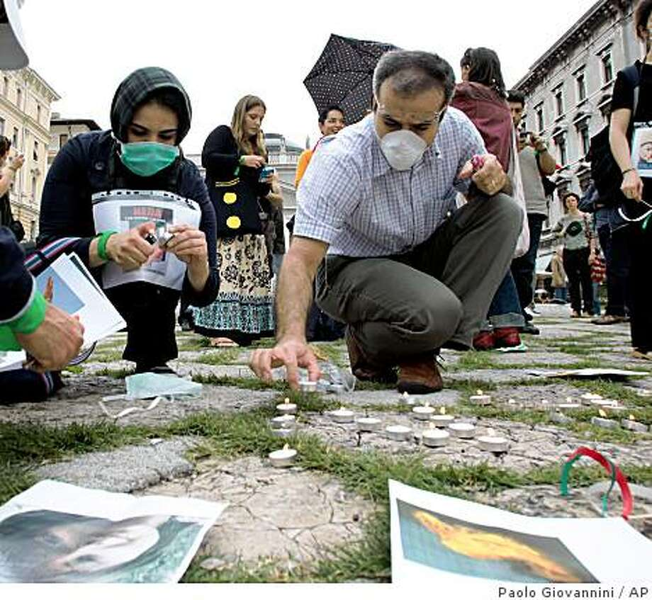 """Activists light candles during a demonstration against the violence in Iran, at the G8 foreign ministers' meeting in Trieste, Italy, Thursday, June 25, 2009. Italy hopes foreign ministers of the industrialized Group of Eight meeting Thursday will send Iran a """"tough"""" message over its violent crackdown on protesters, the Italian foreign minister Franco Frattini said. Italy had originally invited Iran to attend the three-day gathering of industrialized nations in Trieste, as a special guest, arguing that Tehran could have an important role to play in stabilizing Afghanistan - a key focus of the meeting. The meeting begins Thursday evening with an official dinner and will end on Saturday, June 27. Photo: Paolo Giovannini, AP"""
