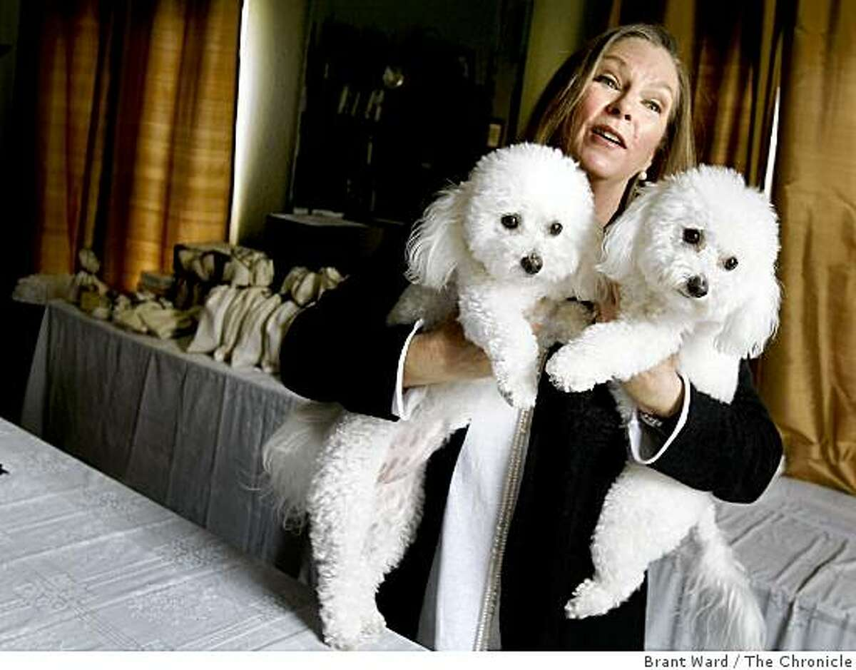 Jeanne Cole holds her two Bichon Frise dogs who have wandered into the shipping area of her home. Jeanne Cole, a former film executive, started an online gift business called Holy Orders. She runs it out of her home in Petaluma, CA