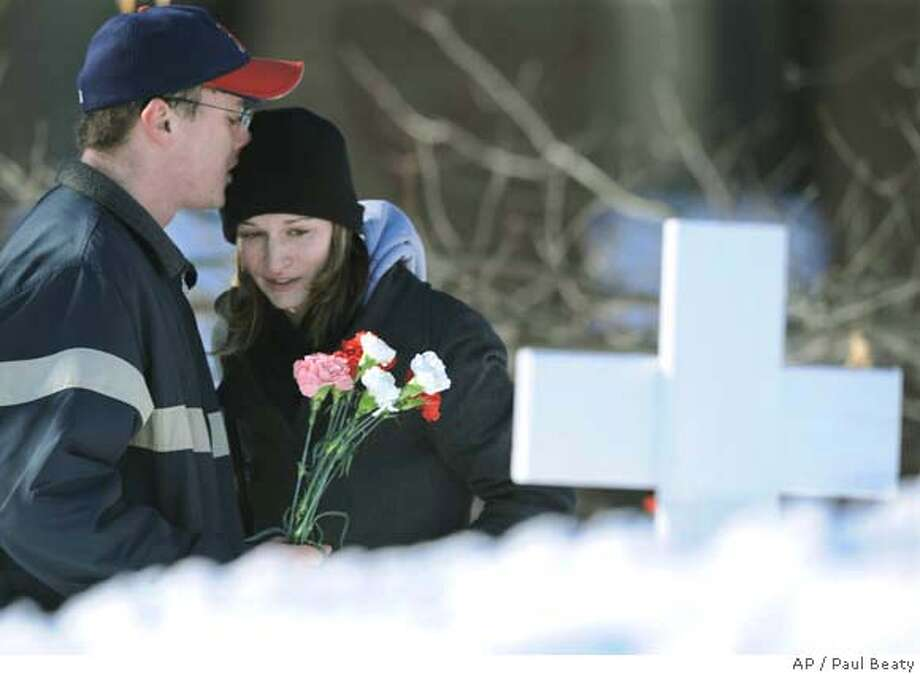 Northern Illinois University student Paige Osborne, right, is comforted by fellow student Matt McBribe after placing flowers at a memorial for the victims of the Northern Illinois University shooting in Dekalb, Ill., Friday, Feb. 15, 2008. (AP Photo/Paul Beaty) Photo: Paul Beaty