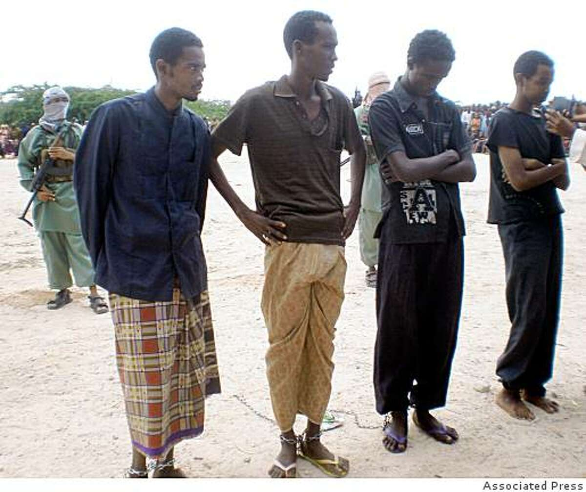 Four men sentenced to have a hand and foot cut off stand in a square in north of Mogadishu, Somalia, Monday June 22, 2009. The Somali Islamic militants faction Alshabab carried out amputations on Thursday on four young men accused of robbery in the capital Mogadishu. Alshabab judge Abdul Haq sentenced the four young men on Tuesday to a cross-amputation, that's the amputation of the right hand and the left foot. They were accused of stealing pistols and mobile phones from Mogadishu residents. Aden Mohamud, Ismail khalif , Jeylani Mohamed, and Abdulkadir Adow were brought in an open ground by Alshabab in their Malah military camp in the notrheastren part of the city, where the the sentence was carried out.