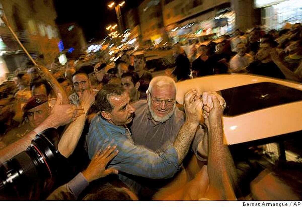 Palestinians welcome Palestinian parliament speaker Abdel Aziz Duaik, center, in the West Bank town of Hebron, Tuesday, June 23, 2009. The Hamas-affiliated speaker of the Palestinian parliament was freed Tuesday from an Israeli prison after serving the bulk of his three-year sentence. (AP Photo/Bernat Armangue)