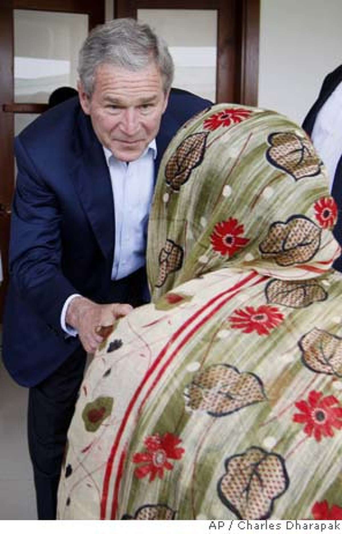 U.S. President George W. Bush greets patients in the outpatient area of the Amana District Hospital in Dar es Salaam, Tanzania, Sunday, Feb. 17, 2008. (AP Photo/Charles Dharapak)