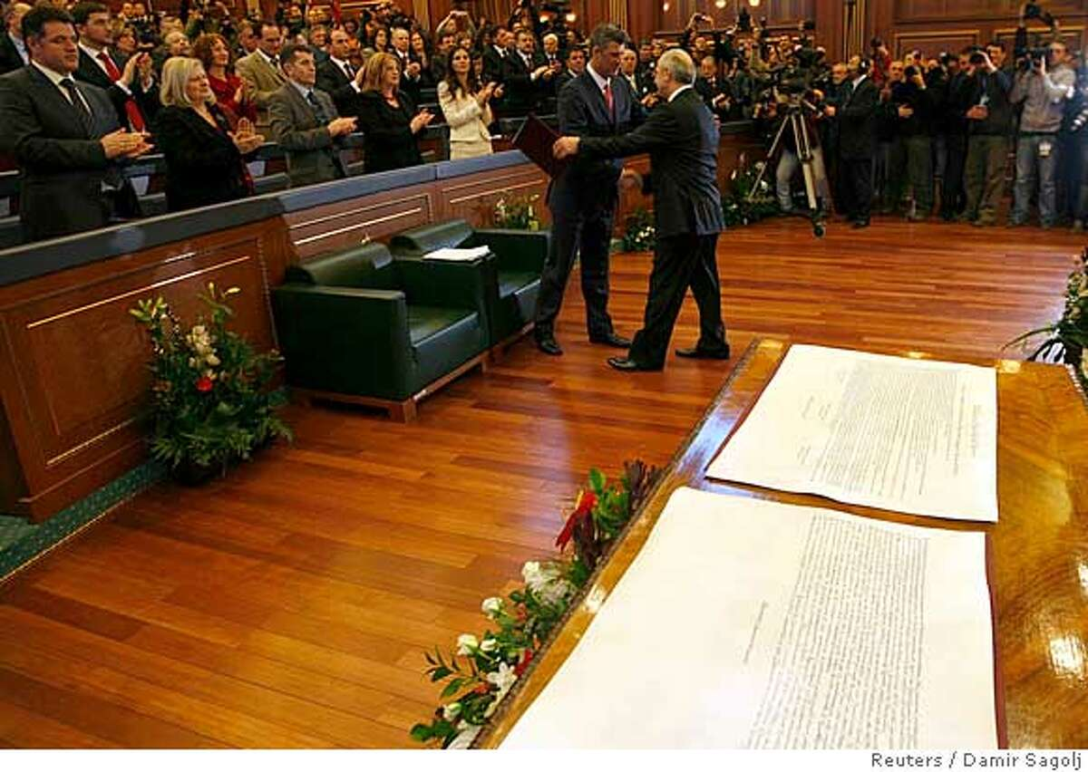 Behind a declaration of independence, Prime Minister Hashim Thaci (L) and President Fatmir Sejdiu shake hands before signing it during a parliament session in Pristina February 17, 2008. REUTERS/Damir Sagolj (SERBIA)