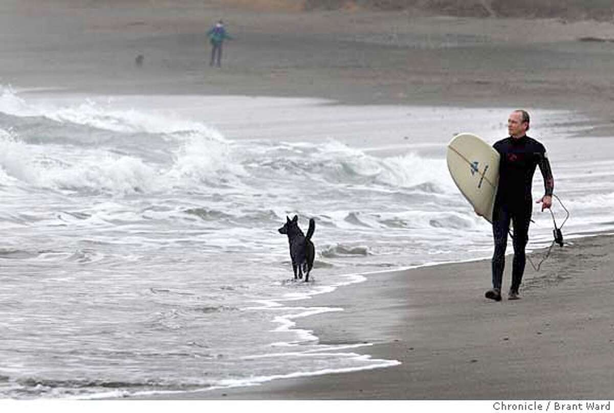 Scott Williams walks down the beach at Linda Mar in Pacifica Sunday. His dog, Violet, doesn't go into the surf to far. But his previous dog, Tadpole, used to go way out into the surf. (Photo by Brant Ward/San Francisco Chronicle)