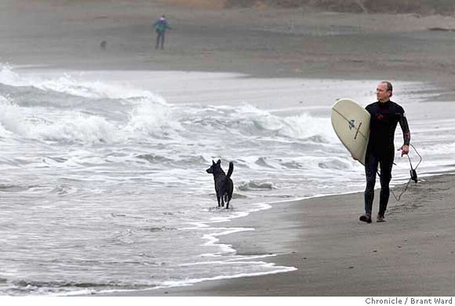 Scott Williams walks down the beach at Linda Mar in Pacifica Sunday. His dog, Violet, doesn't go into the surf to far. But his previous dog, Tadpole, used to go way out into the surf.  (Photo by Brant Ward/San Francisco Chronicle) Photo: Brant Ward