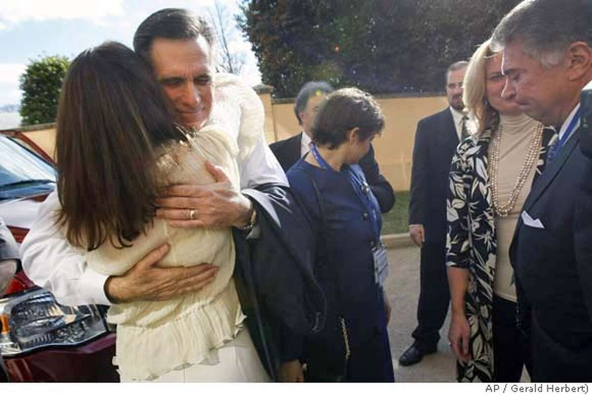 Republican presidential hopeful, former Massachusetts Governor Mitt Romney, hugs unidentified supporters as he leaves the back entrance of the Omni Shoreham Hotel after announcing his withdrawal from the 2008 presidential race in Washington, Thursday, Feb. 7, 2008. (AP Photo/Gerald Herbert)