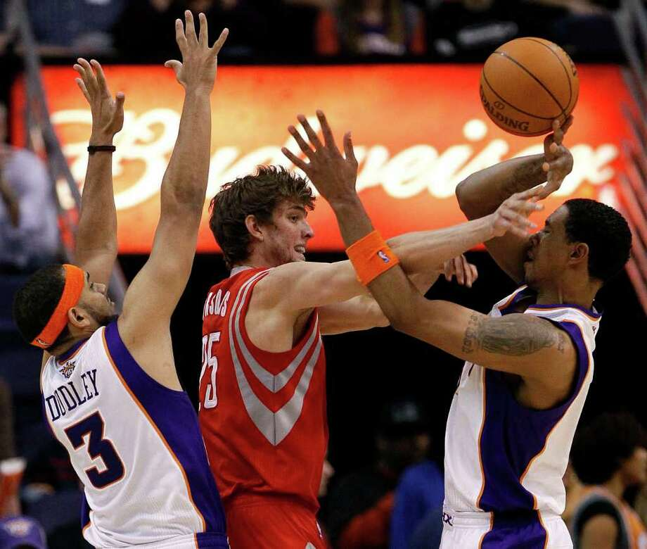 Goran Dragic, center, who contributed 11 points to the Rockets' superb play off the bench at both ends of the floor, deals with pressure from the Suns' Jared Dudley, left, and Channing Frye. Photo: Matt York / AP