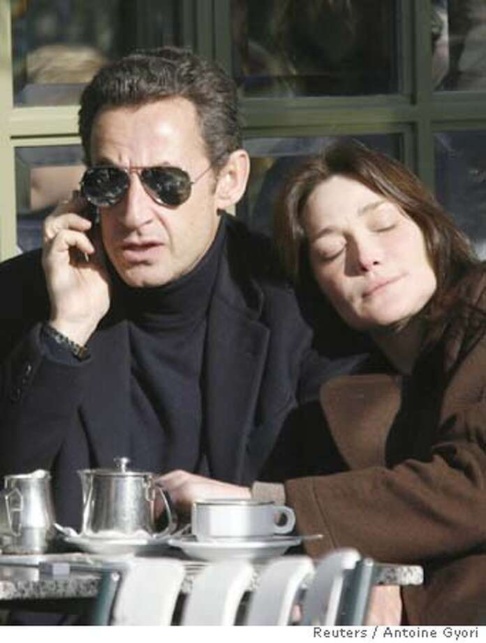 France's first lady Carla Sarkozy (R) relaxes in the sun as she rests her head on the shoulder of President Nicolas Sarkozy who uses the phone while at a cafe terrace in the gardens of the Versailles Chateau near Paris, February 3, 2008, the day after they were married at the Elysee Palace. France's President Sarkozy married supermodel-turned singer Carla Bruni on Saturday just three months after they started dating. REUTERS/Antoine Gyori (FRANCE) Photo: ANTOINE GYORI