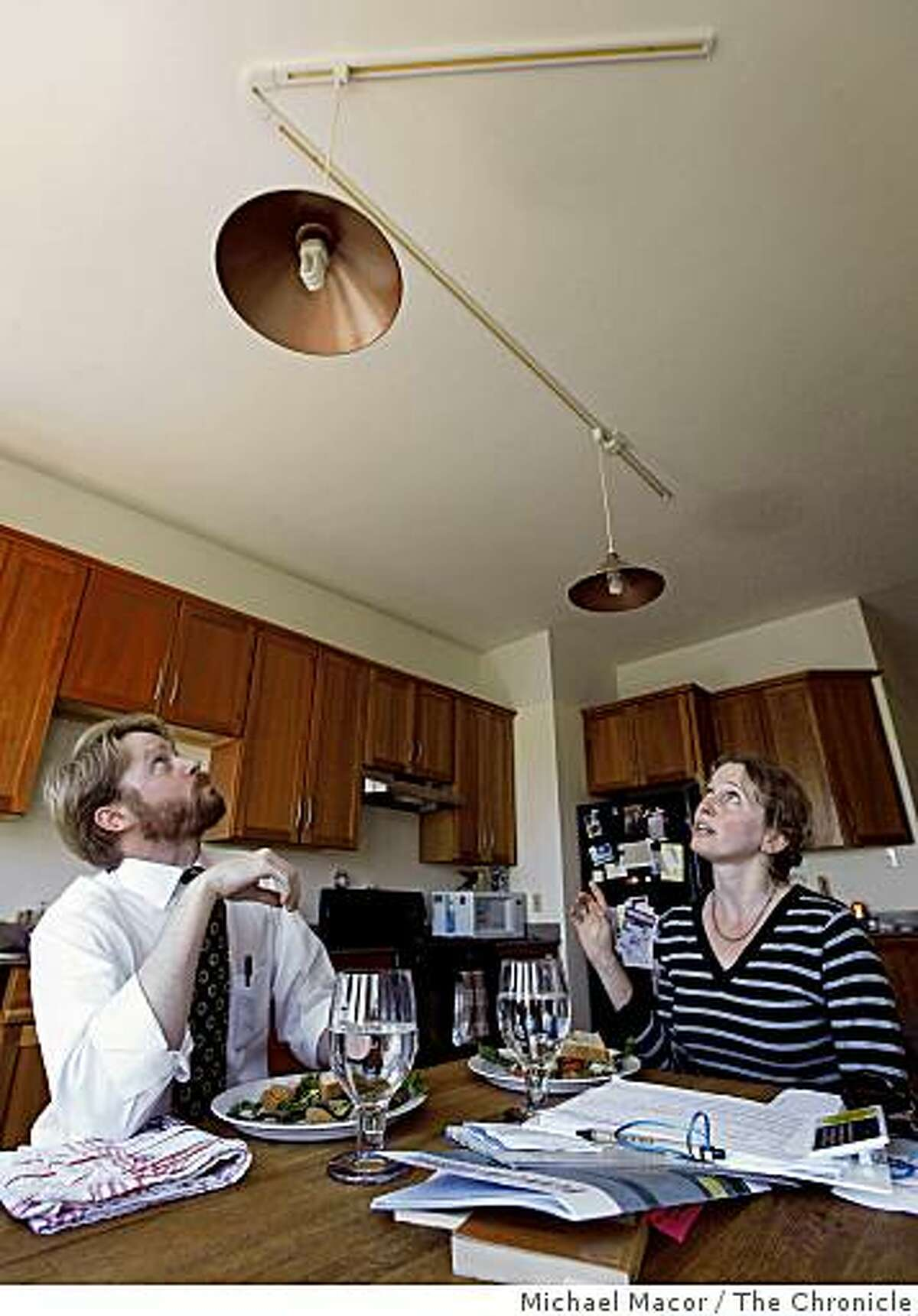 Homeowner, Craig Bridwell and eco consultant, Sara Mossman discusses the types of energy saving lighting fixtures in his home in San Francisco, Calif. on Thursday June 18, 2009.