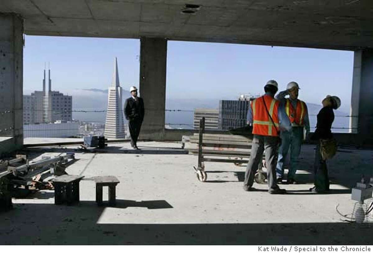 Millennium Partner's, managing director, Richard G. Baumert, left, walks the space with a view of the pyramid building while Millennium Partner's onsite construction manager, Chris Vaughnhulbert, goes over blueprints with Handel Architects' project manager Gerald Sams and project architect Harriet Chang in the penthouse that an anonymous man has agreed to pay $10 million dollars for at the luxury Millennium Tower on Mission Street now under construction on Friday, February 15, 2008 in San Francisco, Calif. Mandatory Credit for photographer, Kat Wade No Sales/Mags out