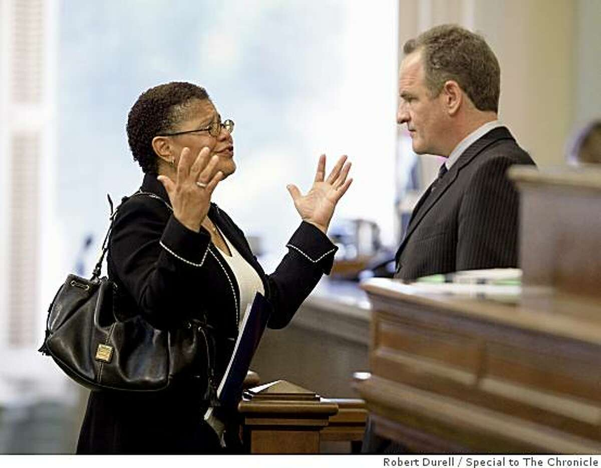 Speaker of the state Assembly Karen Bass (D-Los Angeles), left, speaks with minority leader Sam Blakeslee, right (R-San Luis Obispo) on the floor of the Assembly in Sacramento, California, June 25, 2009. The state legislature is trying to close a $24 billion deficit by July 1, 2009. With time running out, the state Assembly and state Senate debate are trying to close the deficit. But chances of approval are slim to none with Republicans balking at the Democrats' tax proposals and arguing for deeper cuts.
