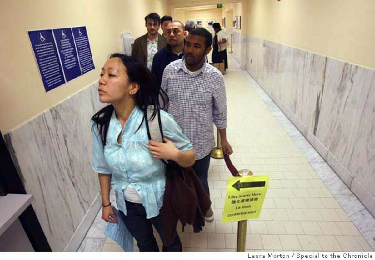 Debbie Kim (left) and Loran Simon (second in line) wait in line along with others voting early for the presidential primaries on Monday afternoon at San Francisco City Hall. (Laura Morton/Special to the Chronicle)