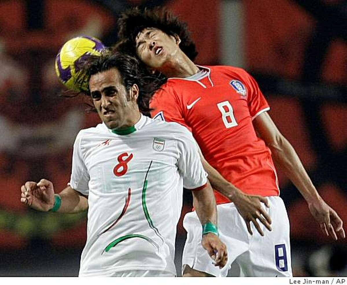 FILE - This June 17, 2009 file photo shows South Korea's Kim Jung-woo, right, fighting for the ball against Iran's team captain Mohammad Ali Karimi, wearing green wristbands, during their 2010 FIFA World Cup Asia group 2 qualifying soccer match at Seoul World Cup Stadium in Seoul, South Korea. (AP Photo/ Lee Jin-man, File)