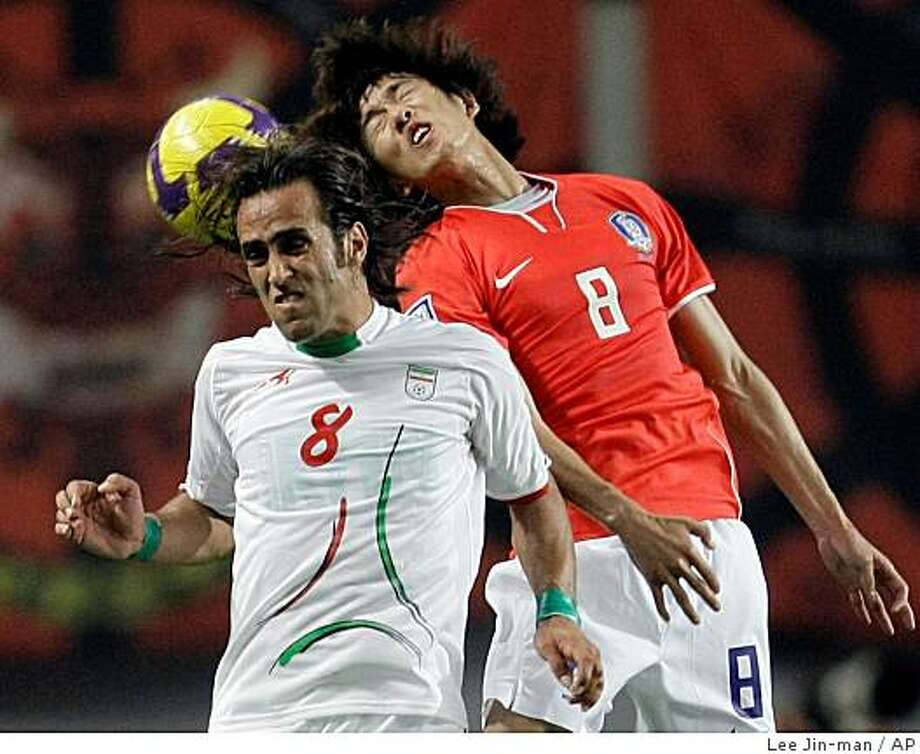 FILE - This June 17, 2009 file photo shows South Korea's Kim Jung-woo, right, fighting for the ball against Iran's team captain Mohammad Ali Karimi, wearing green wristbands, during their 2010 FIFA World Cup Asia group 2 qualifying soccer match at Seoul World Cup Stadium in Seoul, South Korea. (AP Photo/ Lee Jin-man, File) Photo: Lee Jin-man, AP