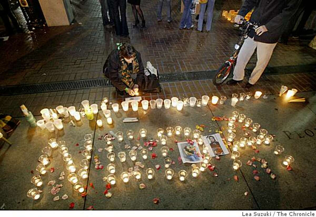 Sharlyn Sawyer lights a candle with others spelling out