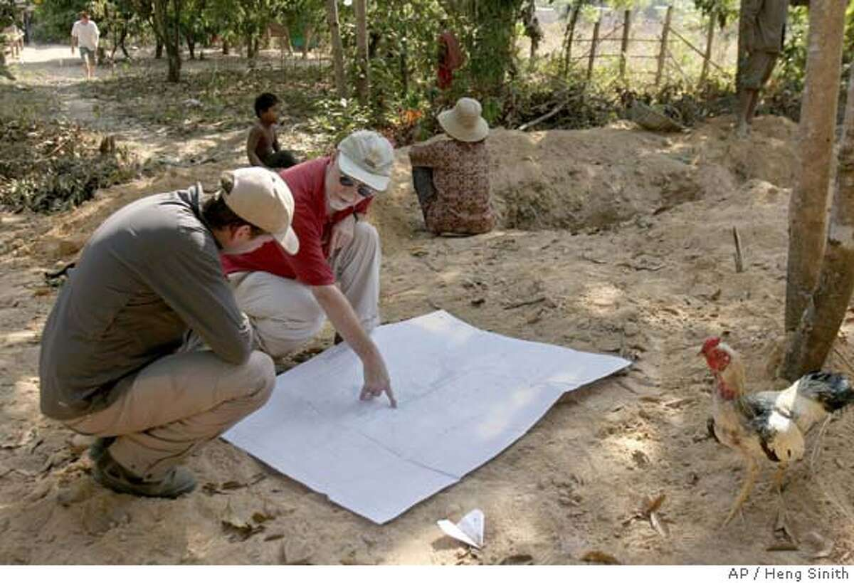 **APN ADVANCE FOR SUNDAY FEB. 17** Australian archaeologists Damian Evans, left, and Roland Fletcher, right, study a map of Angkorian city during a tour of excavation site in Siem Reap province, Cambodia, on Wednesday Jan. 23, 2008. An international research group is now trying to dig up answers to the question about Angkorian hydraulic network as part of its quest to shed more light on the puzzles left since the demise of the Angkor city centuries ago. (AP Photo/Heng Sinith) **APN ADVANCE FOR SUNDAY FEB. 17** PICTURE TAKEN JAN. 23, 2008