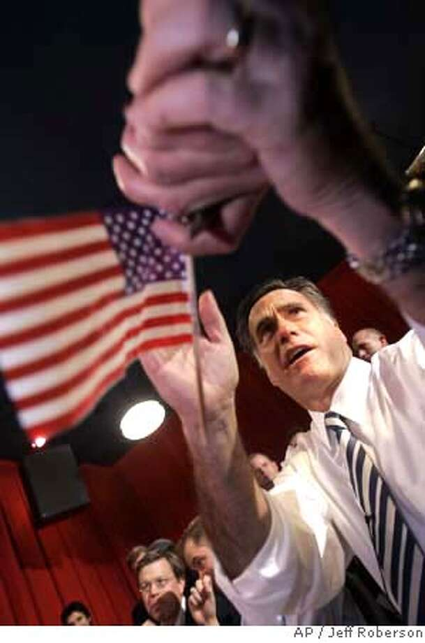 Republican presidential hopeful, former Massachusetts Gov. Mitt Romney, shakes hands with a supporter as he sits down to watch the opening minutes of the Super Bowl at a Dave and Buster's restaurant Sunday, Feb. 3, 2008, in Maryland Heights, Mo. (AP Photo/Jeff Roberson) Photo: Jeff Roberson