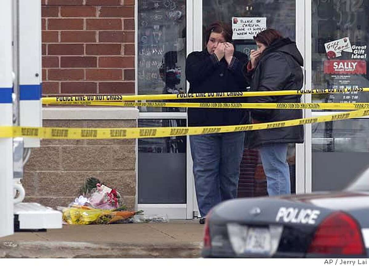 Two unidentified women weep after leaving flowers outside of the Lane Bryant store at the Brookside shopping center in Tinley Park, Ill., Sunday, Feb. 3, 2008. A gunman fatally shot five people at a store in a suburban Chicago strip mall and fled Saturday, prompting police to sweep through neighboring shops looking for the suspect as terrified customers looked on. (AP Photo/Jerry Lai)