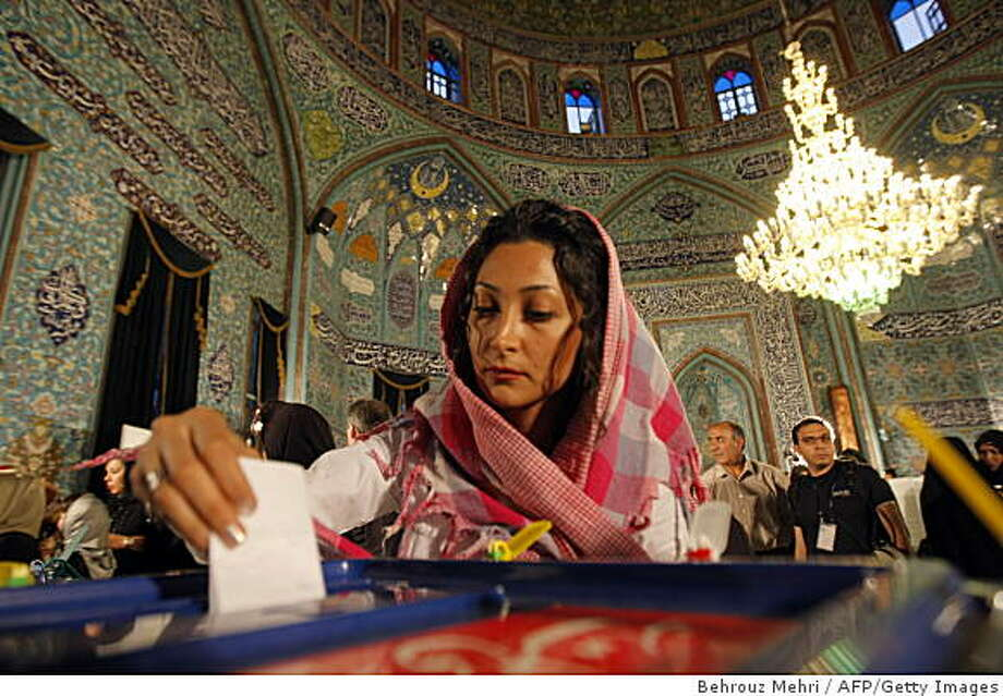 An Iranian woman casts her ballot in the presidential elections in a polling station in Tehran on June 12, 2009. Moderate ex-premier Mir Hossein Mousavi claimed victory in a hotly contested presidential vote in Iran while state news agency IRNA said hardline incumbent Mahmoud Ahmadinejad had won. AFP PHOTO/BEHROUZ MEHRI (Photo credit should read BEHROUZ MEHRI/AFP/Getty Images) Photo: Behrouz Mehri, AFP/Getty Images
