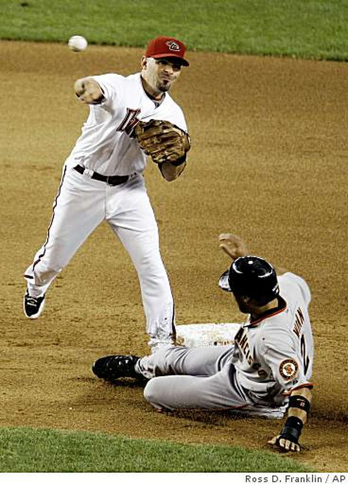 Arizona Diamondbacks' Augie Ojeda, top, throws to first after forcing out San Francisco Giants' Randy Winn in the eighth inning of a baseball game Thursday, June 11, 2009, in Phoenix. (AP Photo/Ross D. Franklin)