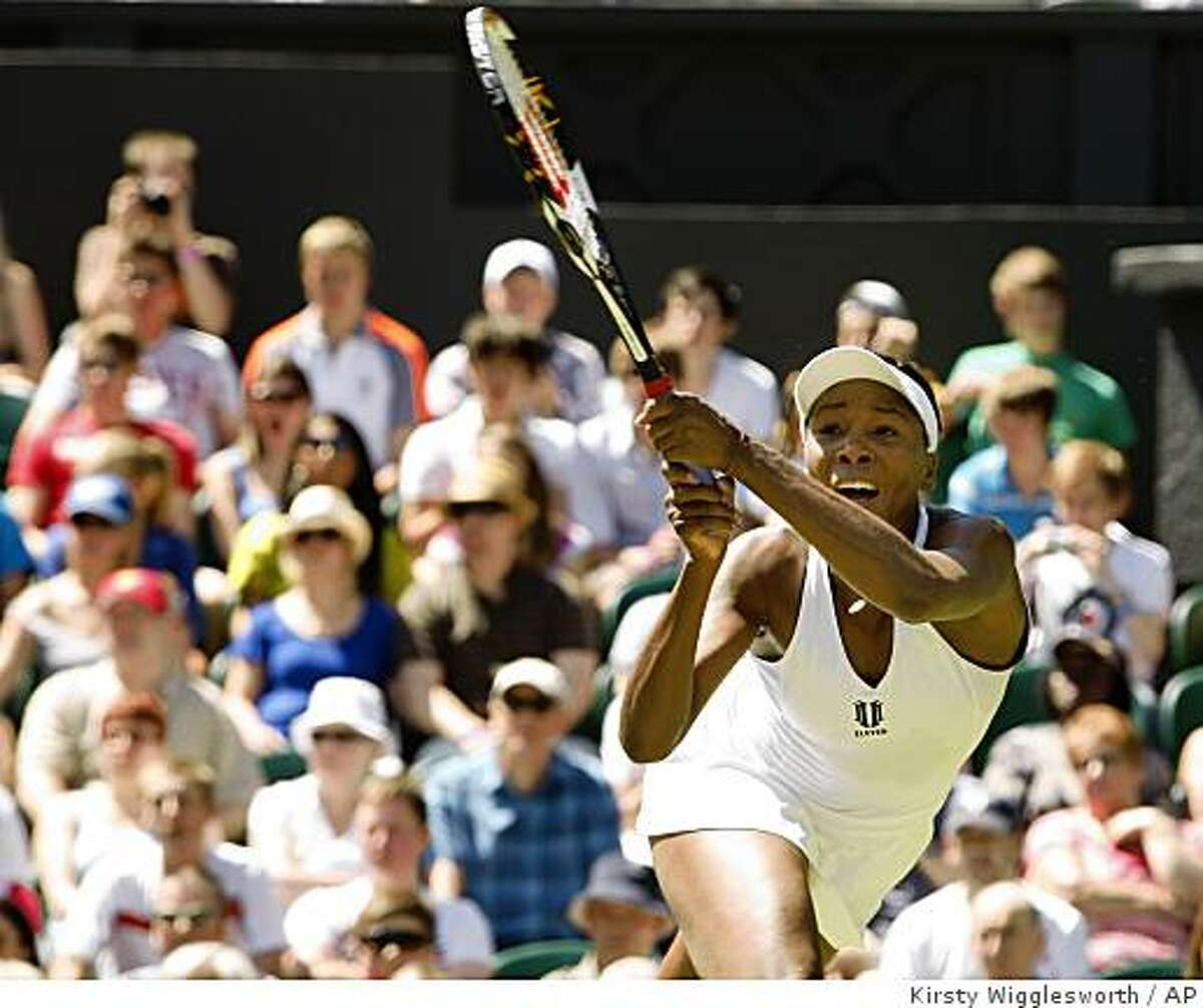 Venus Williams of U.S. plays a return to Stefanie Voegele of Switzerland during their first round singles match at Wimbledon, Tuesday, June23, 2009. (AP Photo/Kirsty Wigglesworth)