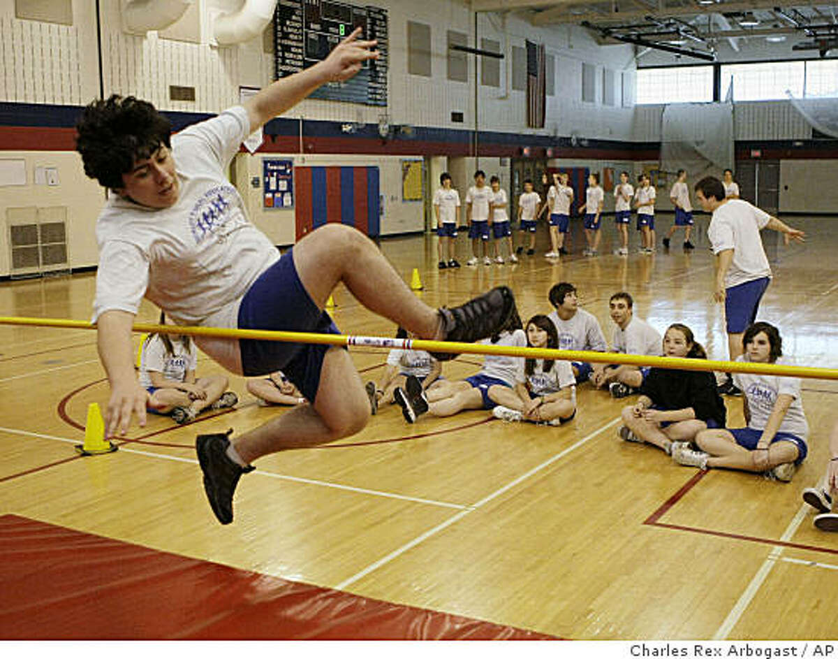 In this photo taken May 19, 2009, middle school student Nick Wasik tries to clear the bars of the high jump at the Emerson Middle School in Niles, Ill., during a physical education class. In the district, middle school students have P.E. for 40 minutes each day. The curriculum is designed to get students moving and appeal to everyone, regardless of athletic ability. Emerson and other schools in the district have one top P.E. programs in the state. (AP Photo/Charles Rex Arbogast)