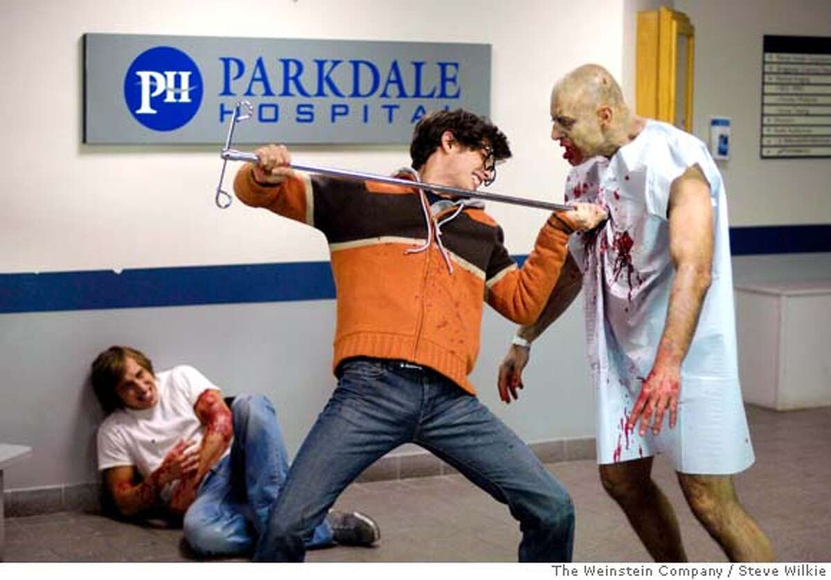 In this image released by The Weinstein Company, Chris Violette, who plays Tony, left, lays wounded as Joe Dinicol, who plays Eliot, center, fights off a zombie in the film,