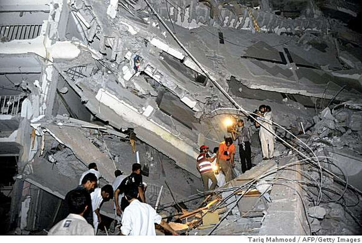 Pakistani volunteers search blast victims in the rubble of the destroyed five-star hotel portion after a bomb blast in Peshawar on June 10, 2009. At least 11 people were killed and 46 injured in a huge bomb blast at the five-star Pearl Continental hotel in the northwestern Pakistani city of Peshawar, a police official said. AFP PHOTO/ Tariq MAHMOOD (Photo credit should read TARIQ MAHMOOD/AFP/Getty Images)