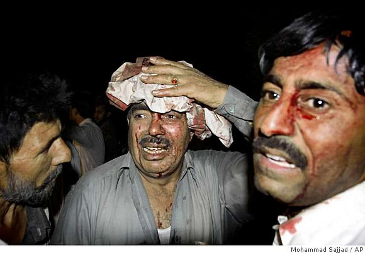 Wounded Pakistani men are seen after an explosion in Peshawar, Pakistan, Tuesday, June 9, 2009. Suicide attackers in a truck launched an assault Tuesday on a luxury hotel commonly used by foreigners in Peshawar, firing guns as they stormed past guards and then setting off a huge blast that killed at least five people and wounded 65 more, Pakistani officials said. (AP Photo/Mohammad Sajjad)