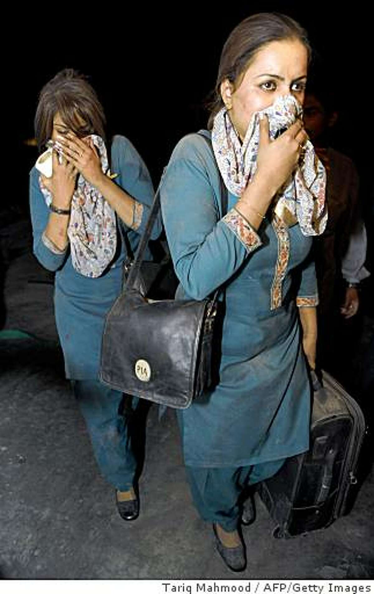 Air hostesses of Pakistan International Airline leave from a five-star hotel after a bomb blast in Peshawar on June 10, 2009. At least 11 people were killed and 46 injured in a huge bomb blast at the five-star Pearl Continental hotel in the northwestern Pakistani city of Peshawar, a police official said. The bomb was hidden in a delivery truck, police and officials said, and was driven up to the five-star Pearl Continental hotel in the high-security Khyber Road area of Peshawar and detonated outside, causing massive devastation.AFP PHOTO/ Tariq MAHMOOD (Photo credit should read TARIQ MAHMOOD/AFP/Getty Images)