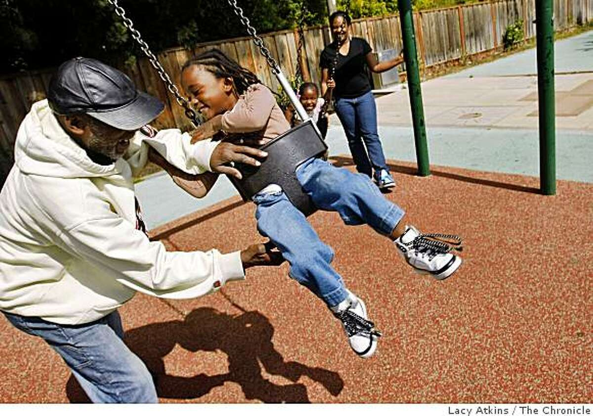 Joe Williams plays with his grandaughter Ebony Williams, 4years old, as Imani Clifton and mother Dana Thomas swing at the Hollis Park, Monday June 8, 2009, in Emeryville, Calif.