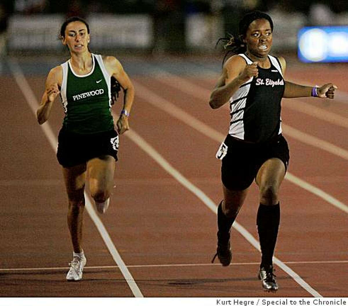 Ashton Purvis of Saint Elizabeth , right, passes Angela Gradiska of Pinewood to win the 200 meter race during the finals of the California State Track and Field Championships in Clovis, Ca Saturday May 6,2009.