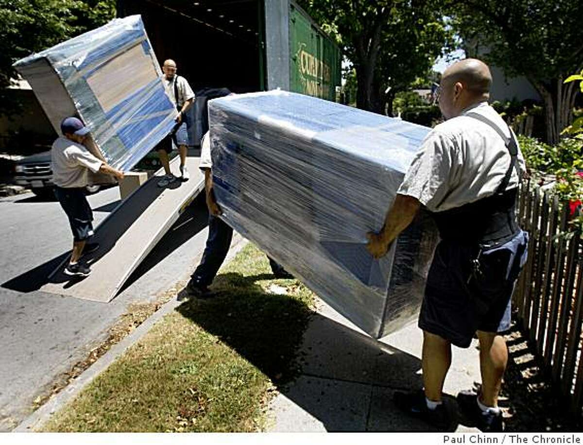Movers from Cummings Moving & Storage unload furniture at a client's home in Burlingame, Calif., on Tuesday, June 23, 2009.