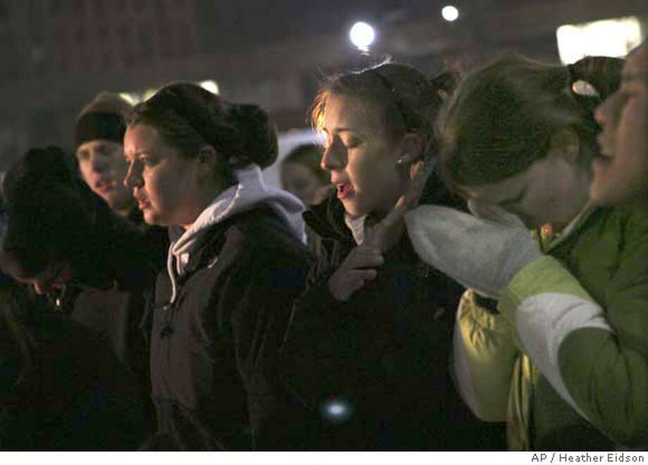 Students, from left, Sara Johnson, Alli Grissom, and Kelly Cohley sing and pray during a vigil near Stevens Hall on the Northern Illinois University Campus Thursday Feb. 14, 2008 after after a shooting left several people dead, including the gunman who shot himself. (AP Photo/Heather Eidson - The Beacon News) *** CHICAGO LOCALS OUT *** CHICAGO/CHICAGOLAND OUT *** CHICAGO LOCAL OUT *** Photo: HEATHER EIDSON