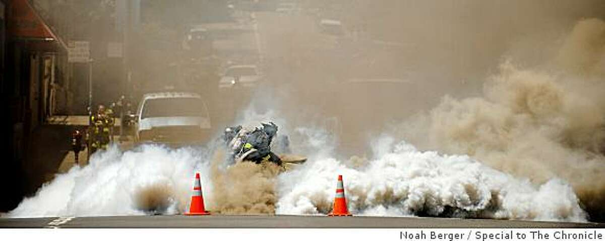 A firefighter battles an underground blaze at Polk and O'Farrell Streets on Friday, June 5, 2009, in San Francisco.