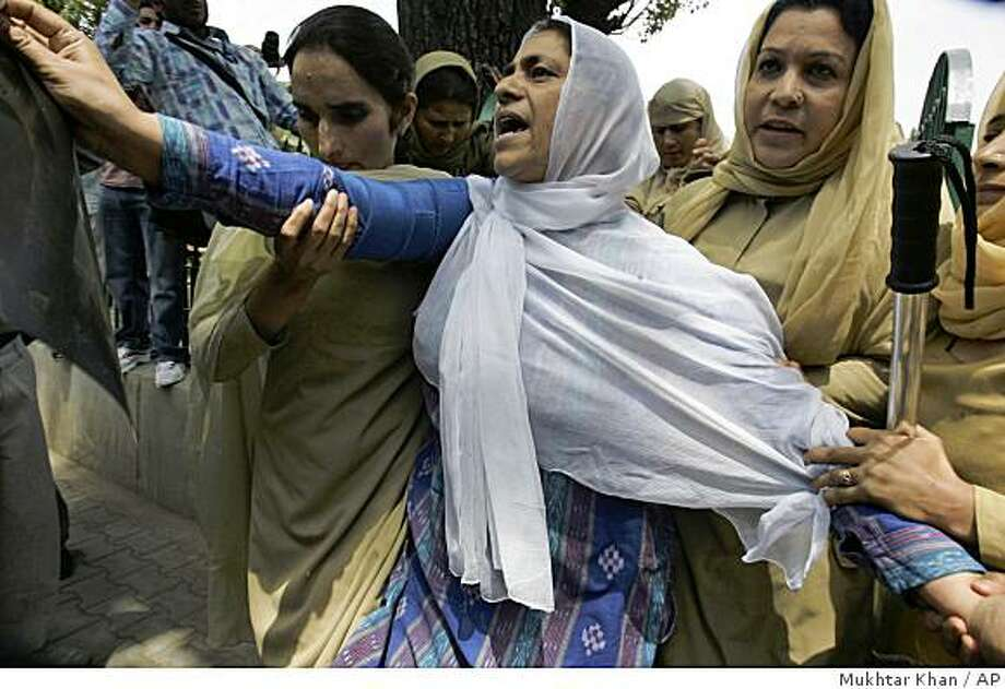 Muslim Khwateen Markaz, or Muslim Women's Organization Chairperson Zamrooda Habib, center, shouts freedom slogans as she is detained by police officers during a protest in Srinagar, India, Monday, June 8, 2009. Forensic reports show that the two young women whose deaths sparked a week of protest in Indian Kashmir were raped, police said, increasing the potential for unrest among demonstrators who blame Indian troops for the killings. (AP Photo/Mukhtar Khan) Photo: Mukhtar Khan, AP