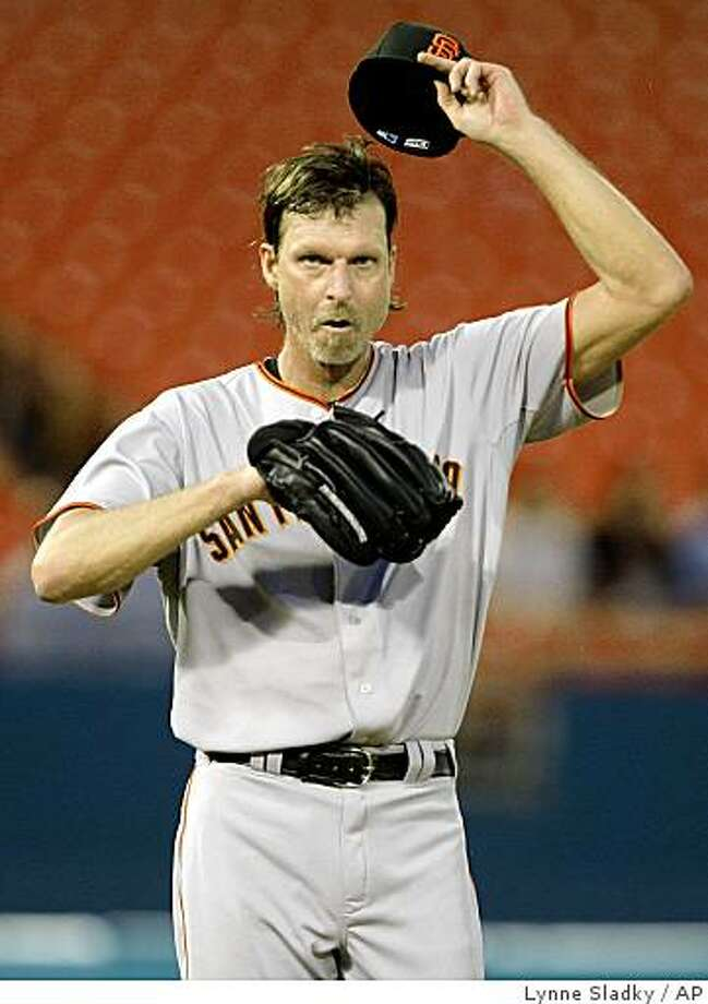 San Francisco Giants starting pitcher Randy Johnson takes off his cap in the fourth inning after Florida Marlins' Brett Carroll hit a triple during a baseball game at Land Shark Stadium in Miami on Monday, June 8, 2009. (AP Photo/Lynne Sladky) Photo: Lynne Sladky, AP