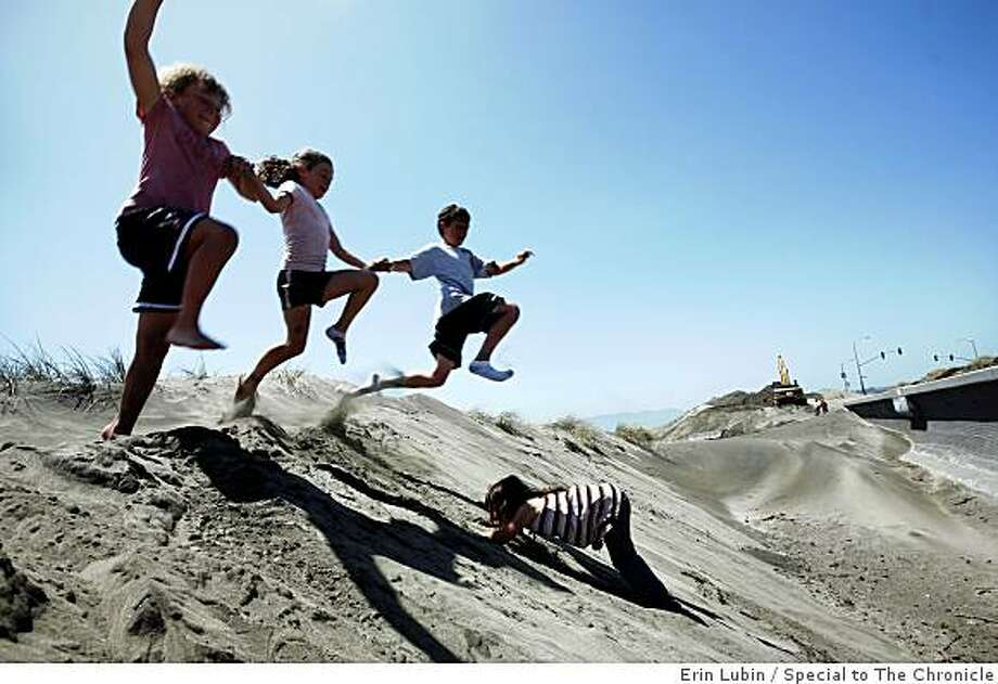 From left, Antonia Maguire, 9, Danielle Maguire, 8, and Gerald Maguire, 10, jump over Victoria Maguire, 5, into a sand dune they say is much bigger since the windy weekend, while in the background, San Francisco Public Works crews finish removing sand from the Great Highway in San Francisco, Calif.  on Monday, June 22, 2009. Public works is scheduled to begin their annual sand clean-up project at the Great Highway tomorrow. Photo: Erin Lubin, Special To The Chronicle