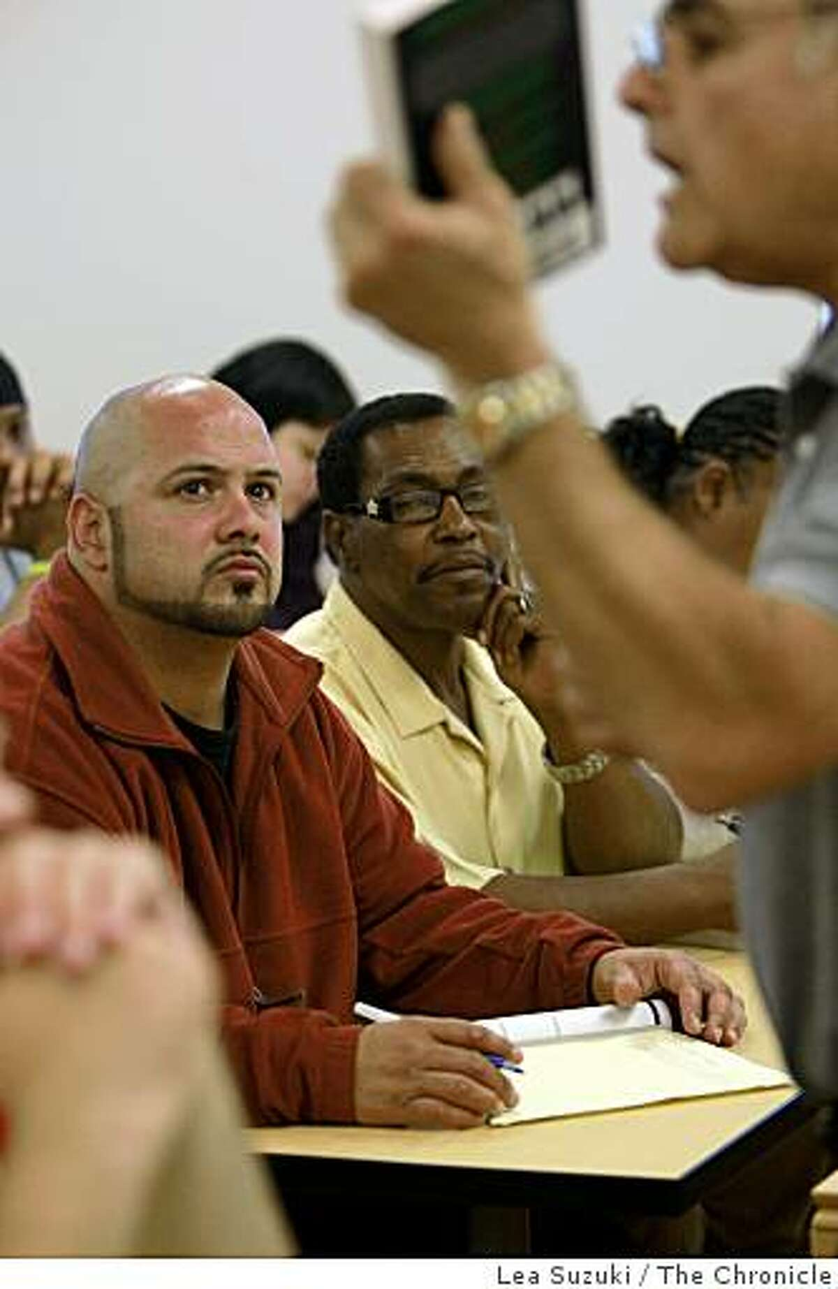 Alex Humphrey (in red jacket) and Eli Crawford (in yellow shirt) listen to Professor Frederick Chavaria, Department Chair Administration of Justice and Fire Science Technology, lecture during class at the City College Mission Campus in San Francisco, Calif. on Tuesday, June 16, 2009.