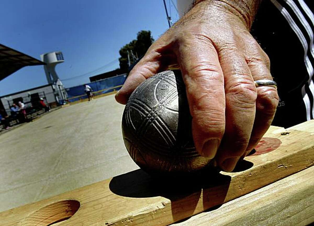 Veteran bocce player Delio Cuneo picks up one of his bocce balls for shooting. The Aquatic Bocce Club of San Francisco, the oldest in the country, hosts the US Bocce Championships at Maritime Park in San Francisco, CA Sunday June 21, 2009.