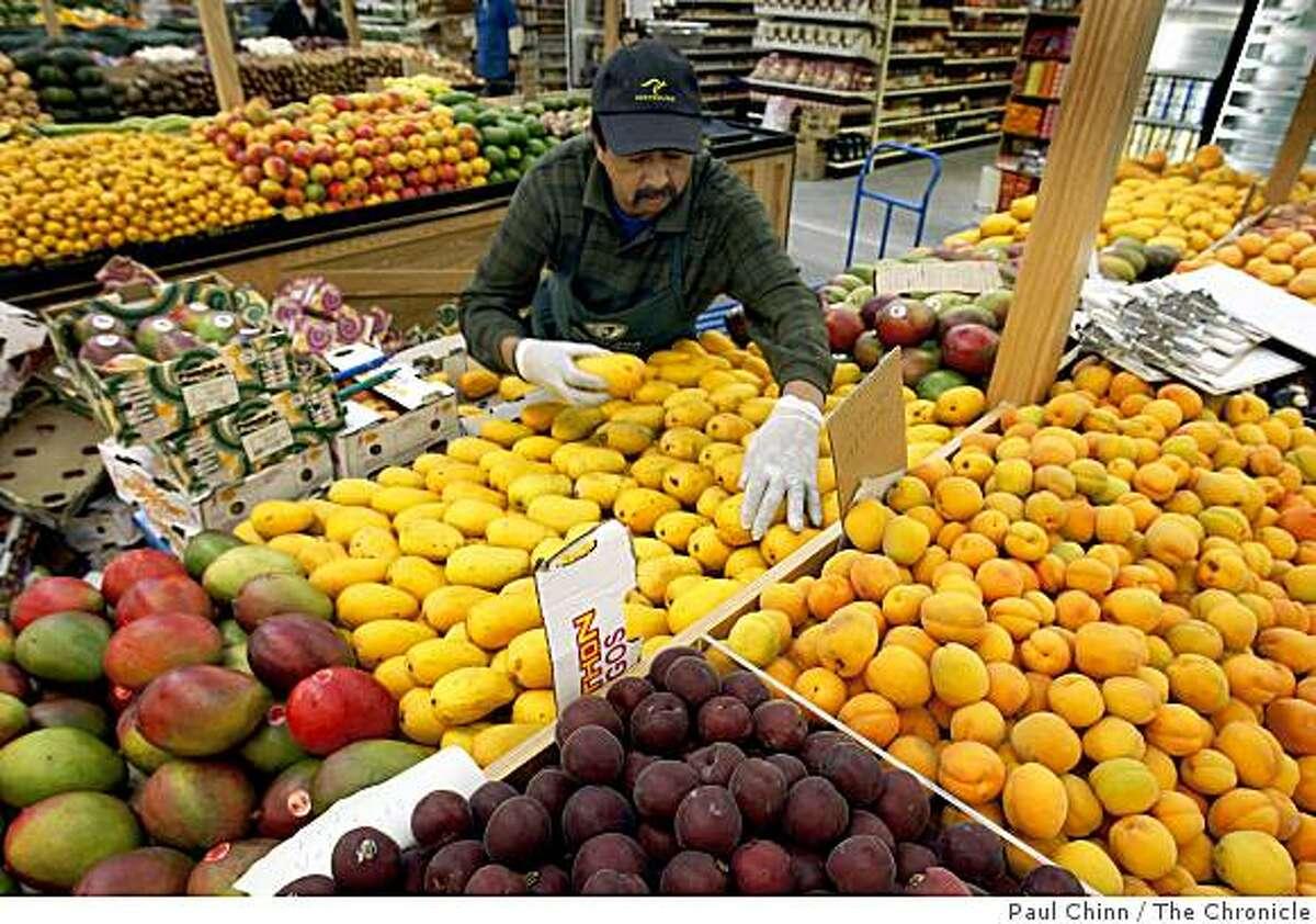 Valentine Saldana stocks the mango section in the produce department of the new Berkeley Bowl West supermarket in Berkeley, Calif., on Wednesday, June 3, 2009.