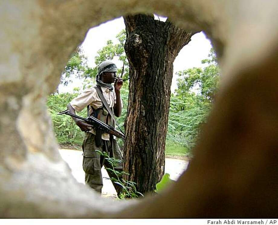 A Islamic fighter is seen through a hole caused by shrapnel in a wall, in Mogadishu, Somalia, Thursday, June 18, 2009, as he man a checkpoint. A suicide bombing outside a hotel in western Somalia killed at least 20 people Thursday, including the national security minister. The Somali president accused al-Qaida of being behind the attack Photo: Farah Abdi Warsameh, AP